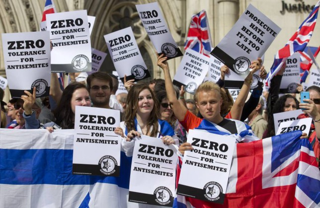 """People hold placards and Israeli and Union flags outide the Royal Courts of Justice as Jewish groups rally in London on August 31, 2014, calling for """"Zero Tolerance for Anti-Semitism"""". Jewish groups demonstrated outside the British High Court as latest figures published by the Community Security Trust reported a spike in anti-semitic attacks on people and property in the UK following the lastest outbreak of violence between Israel and Palestinians in Gaza. AFP PHOTO / JUSTIN TALLIS        (Photo credit should read JUSTIN TALLIS/AFP/Getty Images)"""