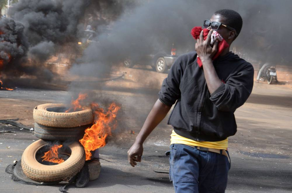 A man holds a hat over his mouth as black smoke billows from tyres set on fire in Niamey, on January 18, 2015 after police fired teargas to disperse a banned opposition demonstration in the capital Niamey, a day after deadly riots erupted over publication by France's Charlie Hebdo magazine of a cartoon depicting Islam's Prophet Mohammed.   Around 300 demonstrators gathered for a march on parliament, but were scattered into surrounding streets and were attempting to regroup, an AFP correspondent reported. AFP PHOTO / BOUREIMA HAMABOUREIMA HAMA/AFP/Getty Images