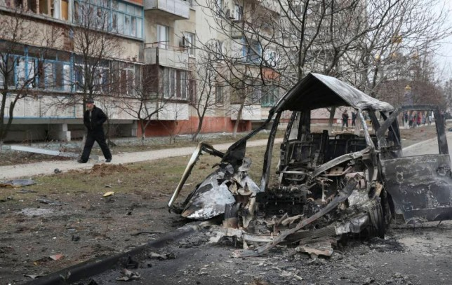 A man walks past a burnt-out vehicle after a shelling by pro-Russian rebels of a residential sector in Mariupol, eastern Ukraine, January 24, 2015. Fifteen people were killed in shelling in the east Ukrainian port city of Mariupol on Saturday, Ukraine's interior ministry said, an attack Kiev blamed on separatist rebels and the Russian military. REUTERS/Stringer (UKRAINE - Tags: POLITICS CIVIL UNREST CONFLICT)