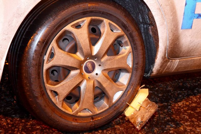 """The crude 'stinger' device found wedged under the wheel of a police car. See SWNS story SWSTING: A woman took out three police cars on one of the busiest nights of the year using homemade """"stingers"""". Emma Sheppard, 33, hammered five large nails through pieces of plywood and put the crude devices under the tyres of panda cars outside a police base. Three Ford Focus response cars drove over them and ground to a halt as they answered emergency calls on New Year's Eve. Sheppard, who was caught by a team investigating anarchist activity in Bristol, admitted recklessly damaging property."""