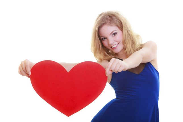Red heart card. Love symbol. Portrait beautiful woman hold Valentine day symbol. Cute blonde girl in blue dress expressing tender feelings. Isolated studio shot Voyagerix/Voyagerix