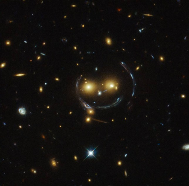 In the centre of this image, taken with the NASA/ESA Hubble Space Telescope, is the galaxy cluster SDSS J1038+4849     and it seems to be smiling. You can make out its two orange eyes and white button nose. In the case of this    happy face   , the two eyes are very bright galaxies and the misleading smile lines are actually arcs caused by an effect known as strong gravitational lensing. Galaxy clusters are the most massive structures in the Universe and exert such a powerful gravitational pull that they warp the spacetime around them and act as cosmic lenses which can magnify, distort and bend the light behind them. This phenomenon, crucial to many of Hubble   s discoveries, can be explained by Einstein   s theory of general relativity. In this special case of gravitational lensing, a ring       known as an Einstein Ring       is produced from this bending of light, a consequence of the exact and symmetrical alignment of the source, lens and observer and resulting in the ring-like structure we see here. Hubble has provided astronomers with the tools to probe these massive galaxies and model their lensing effects, allowing us to peer further into the early Universe than ever before. This object was studied by Hubble   s Wide Field and Planetary Camera 2 (WFPC2) and Wide  Field Camera 3 (WFC3) as part of a survey of strong lenses. A version of this image was entered into the Hubble   s Hidden Treasures image processing competition by contestant Judy Schmidt.