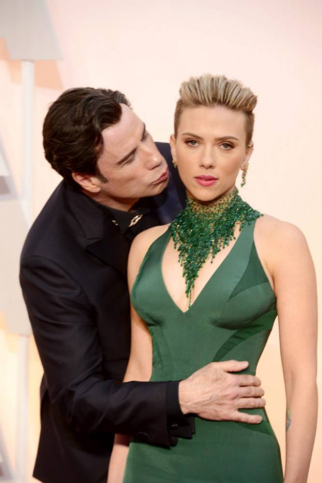 epaselect epa04633184 John Travolta (L) kisses Scarlett Johansson (R) as they arrive for the 87th annual Academy Awards ceremony at the Dolby Theatre in Hollywood, California, USA, 22 February 2015. The Oscars are presented for outstanding individual or collective efforts in 24 categories in filmmaking.  EPA/MIKE NELSON