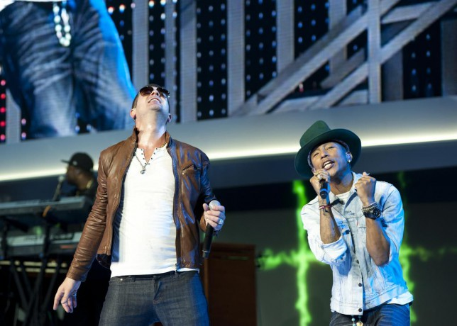 Robin Thicke, left, performs on stage with Pharrell Williams, at the annual Wal-Mart Shareholders meeting in Fayetteville, Ark., Friday June 6, 2014. The meeting drew about 14,000 people, including its workers from around the globe. (AP Photo/Sarah Bentham) AP Photo/Sarah Bentham