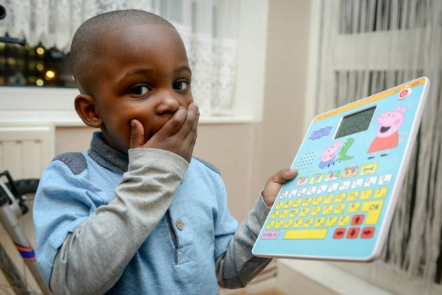 Amari Black, 3, playing with his toy that says ìFuck Youî. See SWNS story SWPEPPA: A three-year-old boy with learning difficulties horrified his parents when some of his first words were ìf*ck youî that he was taught ñ by PEPPA PIG. Amari Blackís parents were ecstatic when their youngest child, who was born with rickets, finally started talking thanks to help from the Peppa Pig Fun and Learn Tablet. But their joy quickly turned to horror when they heard him utter the expletive and realized he had picked it up from the malfunctioning toy. His dad, Garfield, 48, of Waterloo, south east London, noticed that instead of saying ìfind the odd one outî, the toy says ìf**k youÖ odd one outî.