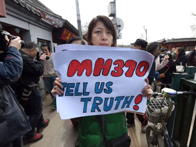 A family member of a Chinese passenger from the missing Malaysia Airlines flight MH370 shows a poster as she leaves after a prayer session at the Yonghegong Lama temple in Beijing on March 8, 2015.   A year on, there remains no evidence to indicate what caused Malaysia Airlines Flight MH370 to vanish or where it ended up, despite the most expensive search operation in history.           AFP PHOTO / GOH CHAI HINGOH CHAI HIN/AFP/Getty Images