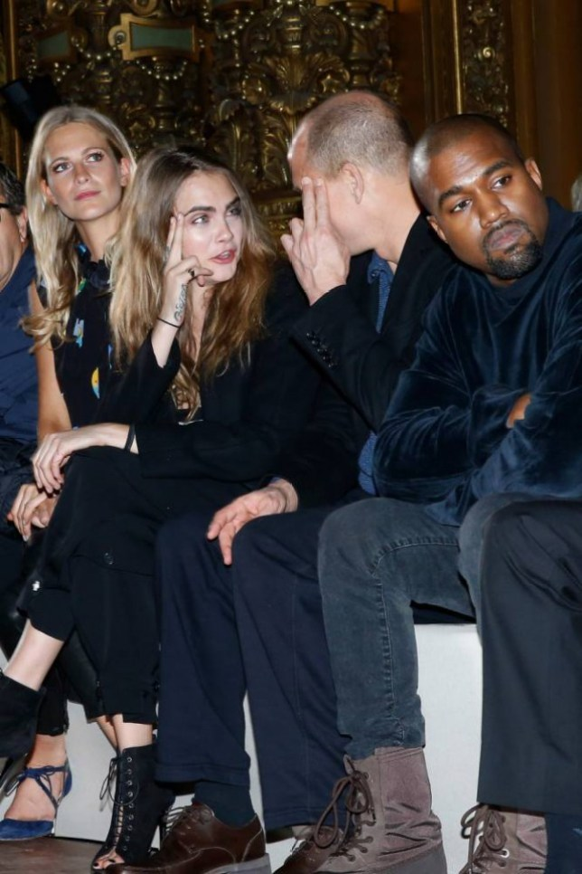 PARIS, FRANCE - MARCH 09:  (L-R) Poppy Delevingne, Cara Delevingne, Woody Harrelson and Kanye West attend the Stella McCartney show as part of the Paris Fashion Week Womenswear Fall/Winter 2015/2016 on March 9, 2015 in Paris, France.  (Photo by Bertrand Rindoff Petroff/Getty Images)
