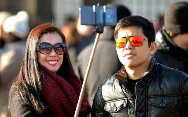 File photo dated 23/01/15 of tourists using a 'selfie stick' in London, as selfie sticks are to be banned from the National Gallery. PRESS ASSOCIATION Photo. Issue date: Wednesday March 11, 2015. Visitors will not be able to use the gadgets - used by people to take photographs of themselves - at the venue because they fall under the category of tripods, which are already prohibited. See PA story ARTS Selfie. Photo credit should read: John Stillwell/PA Wire