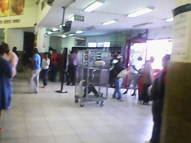 """Pic shows: Rachel Ngema who was stopped by staff at the Spar store when they found a loaf of bread hidden under her jacket was locked in the makeshift cage made out of shopping trolleys """"to teach hear a lesson."""" A supermarket told by police that they could not arrest underage shoplifters is punishing them anyway by locking them inside a metal cage at the entrance as a warning to others. Starving Rachel Ngema, 13, was stopped by staff at the Spar store in the city of Midrand in South Africaís northeastern Gauteng province when they found a loaf of bread hidden under her jacket. But instead of calling her parents, and knowing that the police would refuse to do anything because she was too young, management ordered staff to throw her in the makeshift cage made out of shopping trolleys """"to teach her a lesson."""" And although shoppers reacted angrily after seeing the sobbing girl caged up near the entrance, management refused to budge and warning that they would do the same thing again and had already done the same thing in the past. Shopper Sibongile Mthembu who took this and uploaded it said: """"This is a blatant abuse because this child should be taken to the authorities if she stole, not treated like an animal. Another local, Magdalena Sokhulu, posted: """"Many shops lose a lot from theft but this is not the right way to punish a child of this age."""" A spokesman for the store however said: """"The lock-up punishment is only for under-age children because police do not arrest them. """"We usually release them after several hours of humiliation or at the end of the day before locking up. """"This is the only punishment we have for them and it teaches them a lesson."""" But human rights group SA Human Rights Commission (SAHRC) has slammed the punishment as inhumane and says it is also probably illegal. Spokesman Neldah Sekgobela said: """"We find it unacceptable that in this day and age such cruel, inhumane treatment is carried out. """"The supermarket management should be severely punished for """