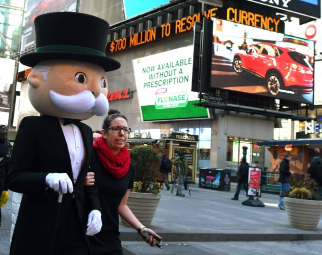 "Mr. Monopoly  is escorted  as he gets ready for photos in Times Square with senior vice president of global brand strategy and marketing, Eric Nyman after they rang Nasdaq's closing bell at the Nasdaq MarketSite on March 19, 2015. The event marked the 80th anniversary of 1935 publication of the board game ""Monopoly"" by Parker Brothers, before the company's 1991 purchase by toy manufacturer Hasbro Inc.    AFP PHOTO /  TIMOTHY  A. CLARY        (Photo credit should read TIMOTHY A. CLARY/AFP/Getty Images)"