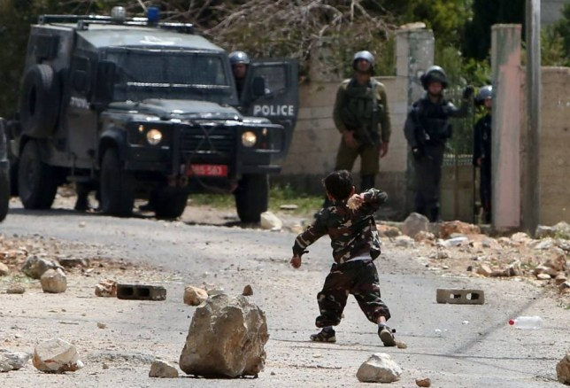 A Palestinian child throws a stone towards Israeli forces during clashes between Palestinian protestors and security forces following a demonstration in support of Palestinian men imprisoned in Israeli jails and against the expropriation of land by Israel, on April 17, 2015 in the village of Kfar Qaddum, near Nablus in the occupied West Bank. AFP PHOTO / JAAFAR ASHTIYEHJAAFAR ASHTIYEH/AFP/Getty Images