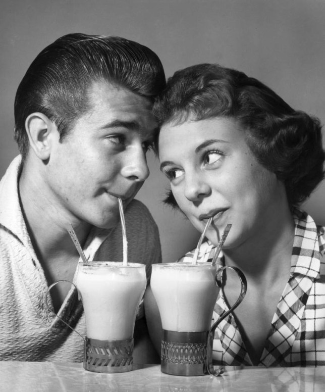 circa 1955:  Studio headshot of a young couple gazing at each other with their foreheads touching as they each sip ice cream sodas through a straw.  (Photo by American Stock/Getty Images)