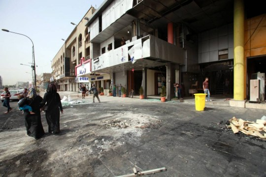 epa04723788 Iraqis stand at the site that was targeted by car bombing, in Mansur district, western Baghdad, Iraq, 28 April 2015. A series of car bombings targeting busy commercial areas in Mansur and Amel districts in Baghdad late 27 April 2015 killed at least 20 civilians and wounded dozens others.  EPA/AHMED JALIL