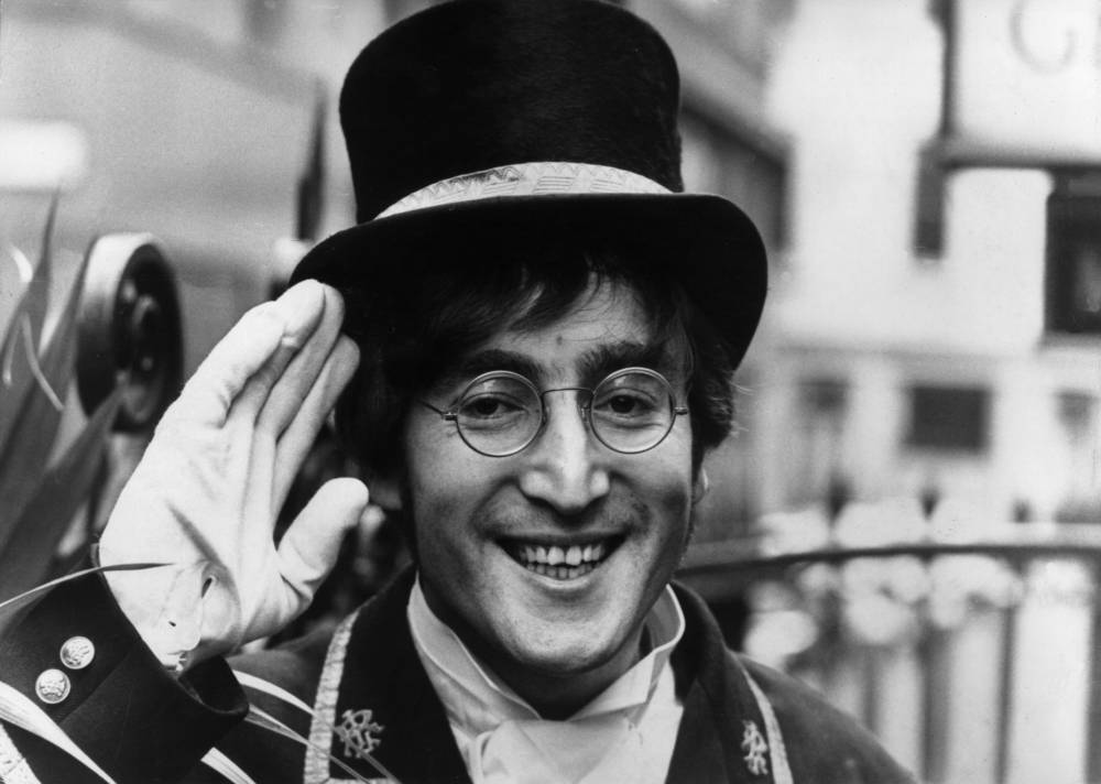 John Lennon saluting and wearing a top hat, dressed as an attendant of a 'members only' club for a skit on the British television series, 'Not Only...But Also,' filmed off Berwick Street in Soho, London, England. (Photo by Express/Express/Getty Images)