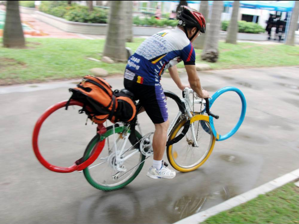 """Mandatory Credit: Photo by Imaginechina/REX Shutterstock (4774943b) Meng Jie rides his refitted bicycle decorated with the five Olympic rings Man creates Olympic rings bicycle, Shenzhen city, Guangdong province, China - 13 May 2015 A Chinese man is planning a tour across the country on his refitted bike decorated with the five Olympic rings. Meng Jie, a resident from Beijing, publicized the Beijing Olympics by cycling around the city on the bicycle in 2008. The bike features a unique dual mechanism allowing it to switch between conventional cycling mode and one where the rider uses both arms and legs to give extra power and speed. With the bike in the 2nd mode Meng claims a top speed on the flat well in excess of 100kmh and does 150km plus daily. Meng had been working on the design since 1992 when China was bidding for the 2000 Games. He left his job as a mechanic to work for a sports company, hoping his new employers would help with the bike's unique development. """"I didn't just want the bike to look cool; I wanted the design to be unique,"""" said Meng."""