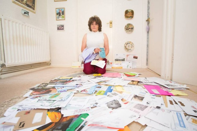 "Jenny Phelps with letters and gifts she has received from various charities. Bristol. 17 May 2015.   See SWNS story SWCHARITY; A widow who has been bombarded with more than 1,000 begging letters from charity after setting up just two direct debit donations has criticised charities for ""preying on her good will"".  Generous Jenny Phelps, 65, decided to start giving money to charity following the death of her husband five years ago - as she wanted to do some good.  She set up two direct debits to the International Fund for Animal Welfare (IFAW) and the RSPCA, both for £3 a month and shortly after she also started giving the same amount to BUAV.  But before she knew it, the big-hearted pensioner was receiving around two or three requests per day from charities asking her to donate."