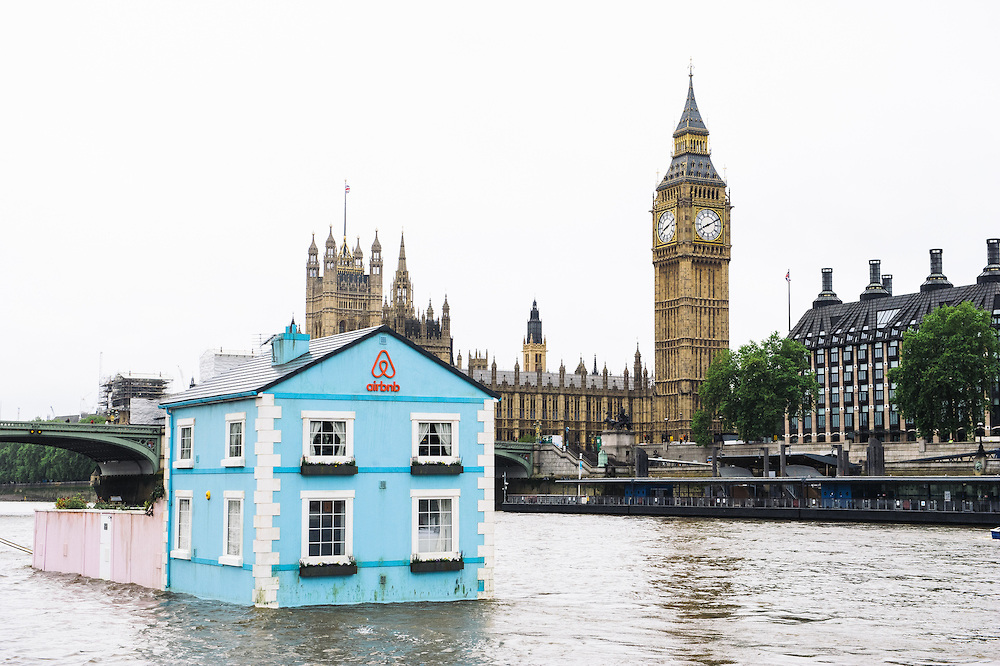 Monday 18th May 2015, London:  AirbnbÕs latest London listing is pictured floating down the River Thames this morning. This pic: The house going past the Houses of Parliament The fully functioning Floating House will sail down the Thames to celebrate new rules that mean that Londoners Ð like the rest of the UK Ð can earn a 15 per cent pay rise* by sharing their homes through sites like Airbnb. Passing under Tower Bridge before gliding past the Shard on its maiden voyage, the House will meander along the river throughout the week until Saturday 22 May. Copyright: © Mikael Buck / Airbnb +44 (0) 782 820 1042 http://www.mikaelbuck.com