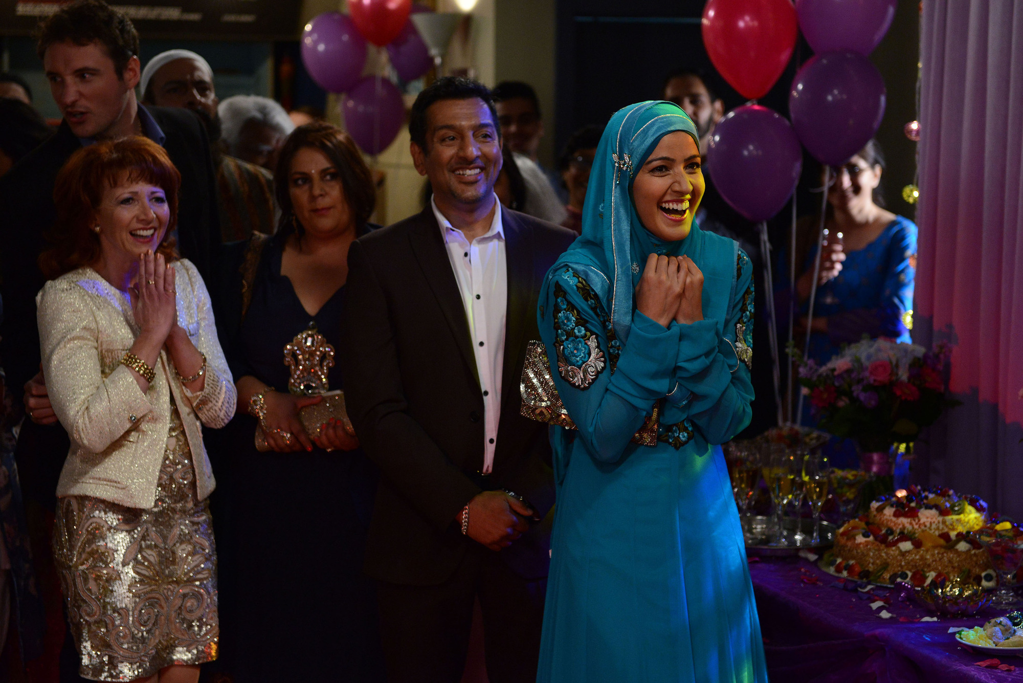 WARNING: Embargoed for publication until 09/06/2015 - Programme Name: EastEnders - TX: 15/06/2015 - Episode: 5085 (No. n/a) - Picture Shows: ***FORTNIGHTLIES PLEASE DO NOT USE (SOAP LIFE and ALL ABOUT SOAP) Shabnam is delighted when the boys perform their dance routine! Martin Fowler (JAMES BYE), Carmel (BONNIE LANGFORD), Masood Ahmed (NITIN GANATRA), Shabnam Masood (RAKHEE THAKRAR) - (C) BBC - Photographer: Steve Peskett