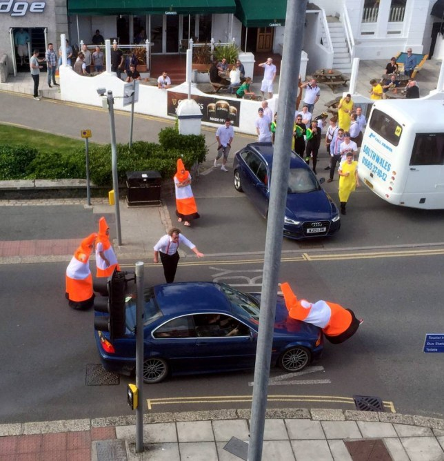 """This collection of human traffic cones caused a stir amongst motorists in Newquay. See SWNS story SWCONES: The group, said to be on a stag-do, manoeuvred themselves around parked cars, briefly bringing traffic to a halt. Although their actions were generally well received, one image shows a cone either appearing to be hit by a car or jumping on a car bonnet. They were moved on by door staff at the nearby Wetherspoon pub around 5pm. Leanne King posted on Facebook: """"To be fair they were hilarious and quite polite to me when I tried to drive off."""""""