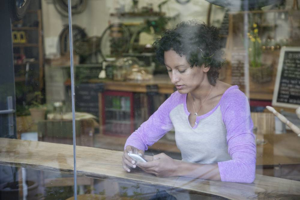 woman looking at smartphone in cafe