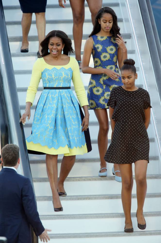 US first lady Michelle Obama (left) accompanied by her daughters, Malia and Sasha (front right) and her mother Mrs. Marian Robinson (back left), steps from an aeroplane, as she arrives at Stansted Airport, Essex, for a visit to the UK, to promote her campaigns for girls' education and better support for military families. PRESS ASSOCIATION Photo. Picture date: Monday June 15, 2015. Mrs Obama, who is travelling with her mother and two daughters and arrives this evening, is due to meet Prince Harry and have tea at Downing Street with David and Samantha Cameron tomorrow. She will also host an event at the Mulberry School for Girls in Tower Hamlets in East London to discuss joint work between America and Britain to boost education for adolescent girls across the world through the Let Girls Learn initiative, championed by her and US president Barack Obama. After London, the party will fly on to Italy to meet US armed services families based in Europe and to visit the Milan Expo as part of the third strand of her work, encouraging healthier diets for children. See PA story POLITICS MichelleObama. Photo credit should read: Chris Radburn/PA Wire