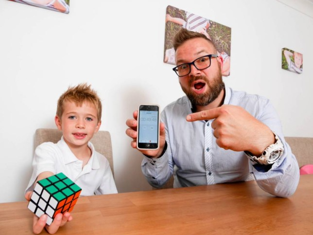 PIC BY DARREN OíBRIEN/MERCURY PRESS (PICTURED: HARRY GILBERT,7, HOLDING HIS RUBIKS CUBE WITH HIS DAD, IAN GILBERT, 38, SHOWING HIS RECORD TIME OF 49 SECONDS) A seven-year-old schoolboy has become an internet sensation after solving a Rubiks Cube in just 49.41 SECONDS - and beating his dad too. Brainbox Harry Gilbert, from Mansfield, Notts, stunned his dad Ian, 38, after solving the 1970s classic puzzle in well under a minute despite only starting to play just weeks ago.  Dad Ian had bought the toy for Harry's birthday in March but ended up playing with the gift himself for weeks before getting an impressive time of one minute 28 seconds himself.  SEE MERCURY COPY