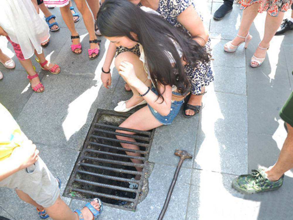 """Pic shows: This Chinese teenager got stuck in drain. A pencil thin Chinese teenager was left stuck after her entire leg got wedged in a storm drain. The girl who was not named but is apparently a teenager had been walking down the street in Mianyang City, in south-west China's Sichuan Province while using her mobile phone to text a friend. She had not been properly looking where she was going, and when she stepped on a drain her thin legs went straight through the grille leaving her foot wedged tight. Other pedestrians tried to help her free her leg, but after realising that she was completely stuck, called the fire brigade who arrived and freed her after a 45 minute ordeal. Fire brigade spokesman Ming Lai said: """"We managed to remove the bars and quickly freed her once we arrived at the scene. Her leg was a bit scratched and bruised and numb from being squeezed through the bars, but she quickly recovered and not need hospital treatment."""" Eyewitness Jun Niu who posted snaps of her ordeal said: """"she was more embarrassed than anything else, she had covered her face up with her hands when people were gathered around and it's clear she didn't want to be there. """"She was incredibly thin though, I reckon normally nobody would be able to lose a foot down there but the bars were a bit bent so I guess that was why it happened."""" (ends)"""