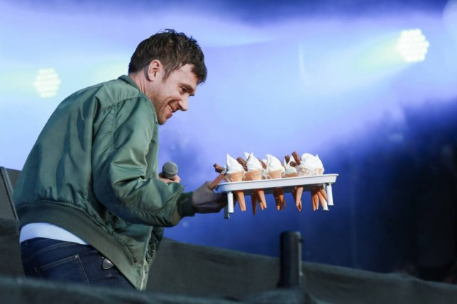 LONDON, ENGLAND - JUNE 20:  Damon Albarn of Blur jumps off stage and hands ice cream cones to fans on day two of British Summer Time 2015 at Hyde Park on June 20, 2015 in London, United Kingdom.  (Photo by Christie Goodwin/Redferns via Getty Images)