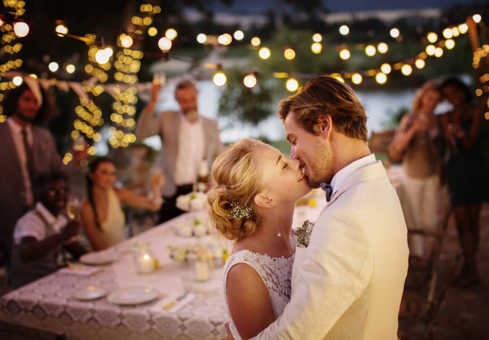 Young couple kissing during wedding reception in domestic garden