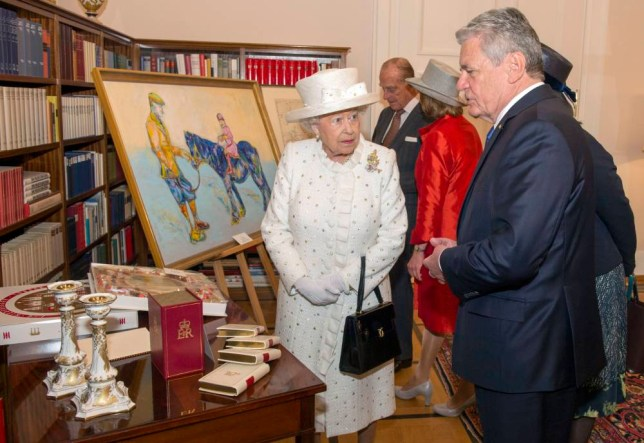 """Queen Elizabeth II and Germany's Federal President Joachim Gauck exchange gifts at his official Berlin residence, Bellevue Palace, on the first full day of her state visit to Germany. A gift of a stylised painting of the Queen sat on a pony prompted the monarch to declare """"that's a funny colour for a horse"""" when the German president gave her the artwork. PRESS ASSOCIATION Photo. Picture date: Wednesday June 24, 2015. Artist Nicole Leidenfrost had painted a young Princess Elizabeth riding a blue coloured pony - which had flecks of yellow and green - with the Queen's father George VI also in the image holding the animal's reins. See PA story ROYAL Queen. Photo credit should read: Arthur Edwards/The Sun/PA Wire"""