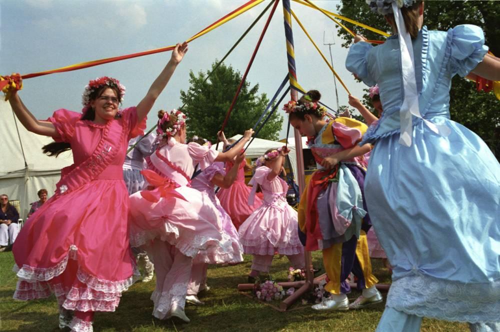 Children dancing around the Maypole at a summer fair in Dulwich park, London.