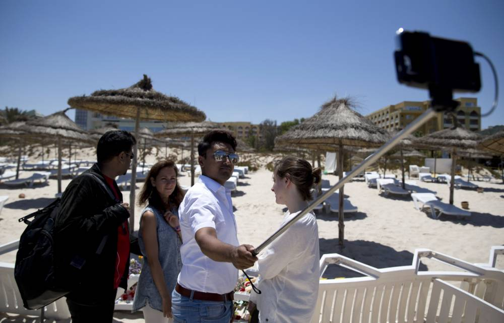 A tourist ( identified as Labour parliamentary candidate Amran Hussain, 29,) uses a selfie-stick to took a picture at the site of a shooting attack on the beach in front of the Riu Imperial Marhaba Hotel in Port el Kantaoui, on the outskirts of Sousse south of the capital Tunis, on June 27, 2015. The Islamic State (IS) group claimed responsibility on June 27 for the massacre in the seaside resort that killed nearly 40 people, most of them British tourists, in the worst attack in the country's recent history. AFP PHOTO / KENZO TRIBOUILLARDKENZO TRIBOUILLARD/AFP/Getty Images