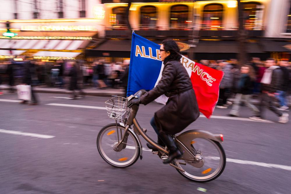 PARIS, FRANCE - JANUARY 11: A woman rides a bicycle holding a French flag during a unity rally in Paris led by French president Francois Hollande and other world leaders following the recent terrorist attacks, January 11, 2015 in Paris, France.  An estimated one million people converged in central Paris for the Unity March in solidarity with the 17 victims of this week's terrorist attacks which began on Wednesday, January 8, 2014 with an attack on French satarical magazine Charlie Hebdo and continued through Friday with attacks at a printing company and a Kosher supermarket. Three suspects were killed in seiges while a fourth, Hayat Boumeddiene, 26, is wanted in connection with the murder of a policewoman.  (Photo by Richard Bord/Getty Images)