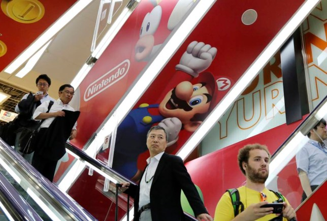 Shoppers move on an escalator under Nintendo's Super Mario characters at an electronics store in Tokyo, Monday, July 13, 2015. Satoru Iwata, who led Japanese video game company Nintendo Co. through years of growth with its Pokemon and Super Mario franchises, died on the weekend of a bile duct tumor, the company said Monday. He was 55. (AP Photo/Koji Sasahara)