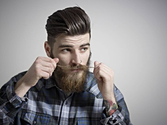 Portrait of young man twisting his moustache. Hipster