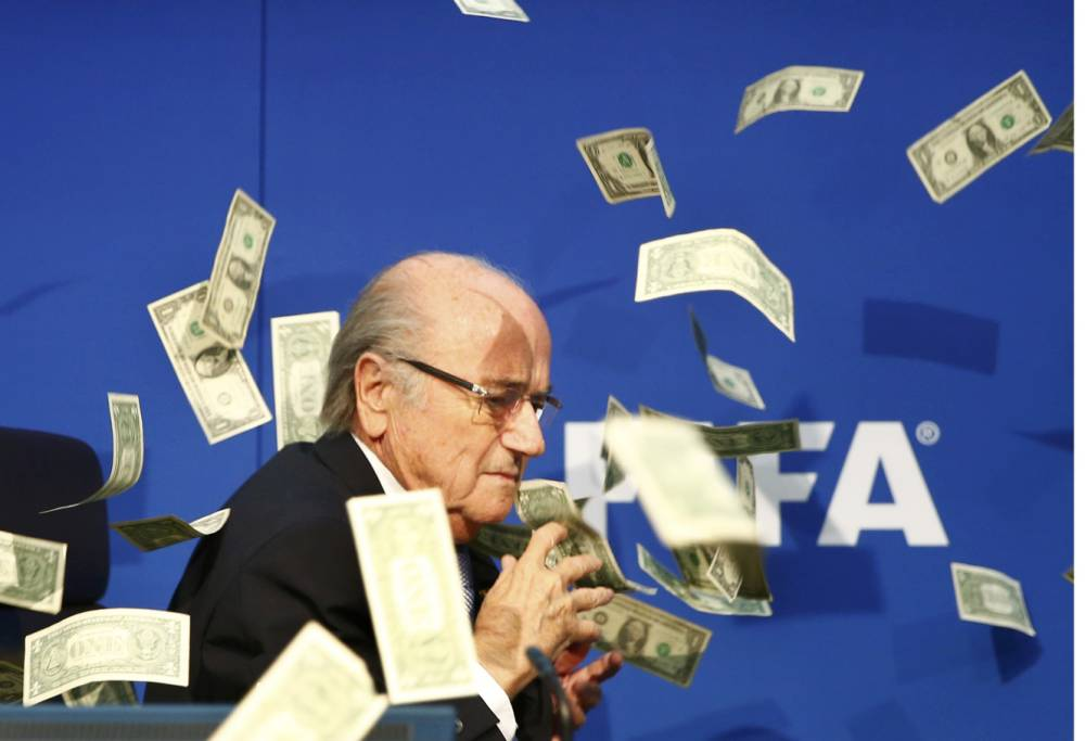 BrItish comedian known as Lee Nelson (unseen) throws banknotes at FIFA President Sepp Blatter as he arrives for a news conference after the Extraordinary FIFA Executive Committee Meeting at the FIFA headquarters in Zurich, Switzerland July 20, 2015. World football's troubled governing body FIFA will vote for a new president, to replace Sepp Blatter, at a special congress to be held on February 26 in Zurich, the organisation said on Monday. REUTERS/Arnd Wiegmann TPX IMAGES OF THE DAY