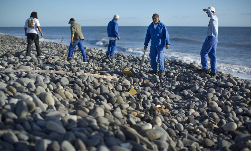 Workers for an association responsible for maintaining paths to the beaches from being overgrown by shrubs, search the beach for possible additional airplane debris near the area where an airplane wing part was washed up, in the early morning near Saint-Andre on the north coast of the Indian Ocean island of Reunion Friday, July 31, 2015. A barnacle-encrusted wing part that washed up on the remote Indian Ocean island could help solve one of aviation's greatest mysteries, as investigators work to connect it to the Malaysia Airlines Flight 370 that vanished more than a year ago with 293 people aboard. (AP Photo/Ben Curtis)