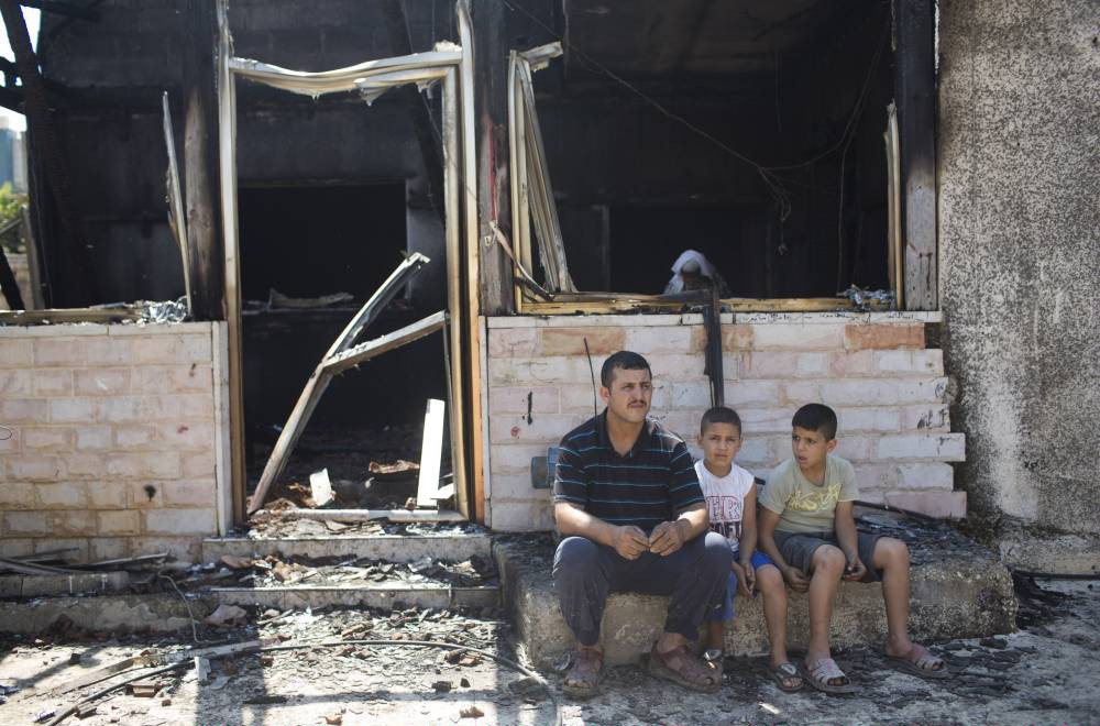 DUMA,WEST BANK - JULY 31:   Family members and relatives of 18 month old baby, Ali Saad-Dawabsheh, view the remains of their house after a fire which was suspected to have been set by Jewish extremists on July 31, in the Palestinian village of Duma, West Bank.  A house fire in the Palestinian village of Duma, West Bank, suspected to have been set by Jewish extremists, killed an 18-month-old Palestinian child, injured both parents and a four year old brother. (Photo by Oren Ziv/Getty Images)