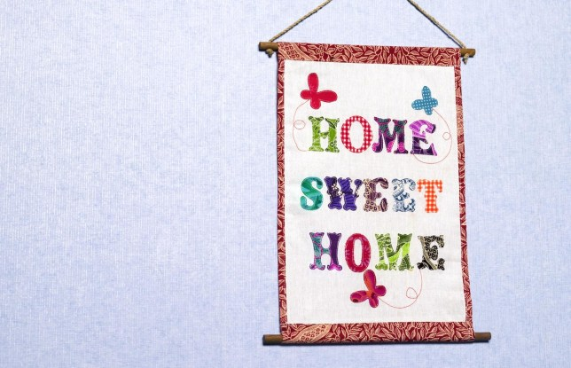 Home sweet home sign hanging on a wall Peter Dazeley/Peter Dazeley