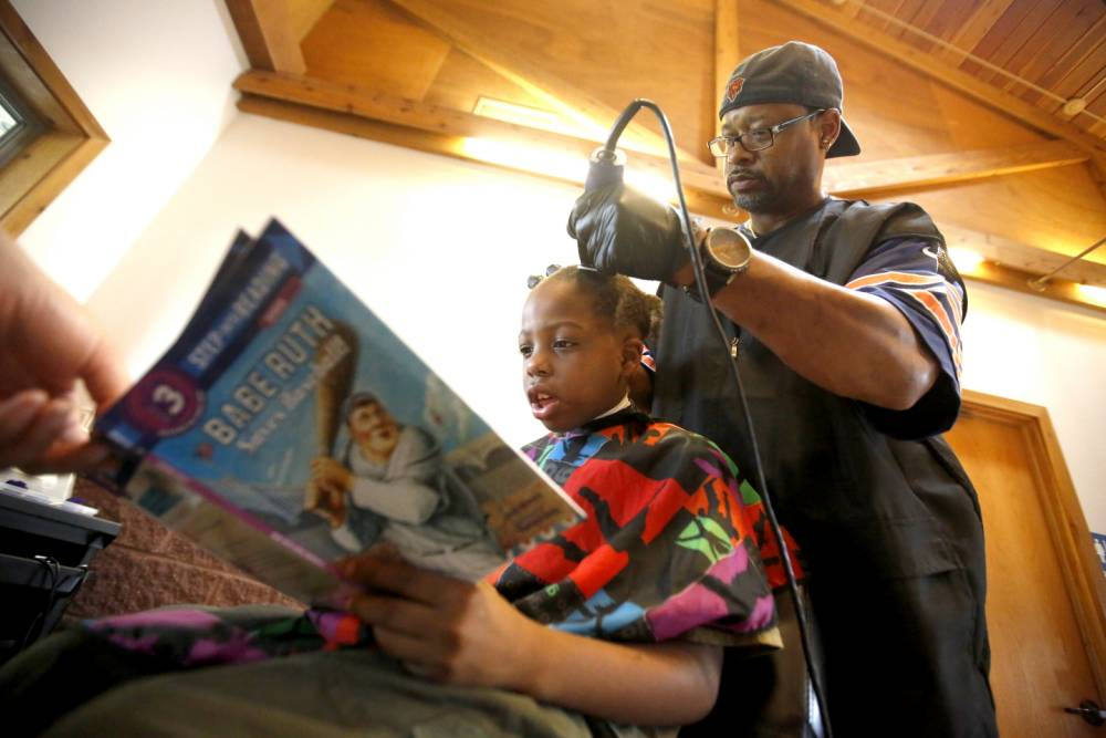 In a Saturday, Aug. 8, 2015 photo, Courtney Holmes, right, listens to Jeremiah Reddick, 9, of Dubuque, as he reads while receiving a free haircut during the Back to School Bash in Comiskey Park, in Dubuque, Iowa. Holmes offered his services to children who read while getting their hair cut.(Mike Burley/Telegraph Herald via AP)