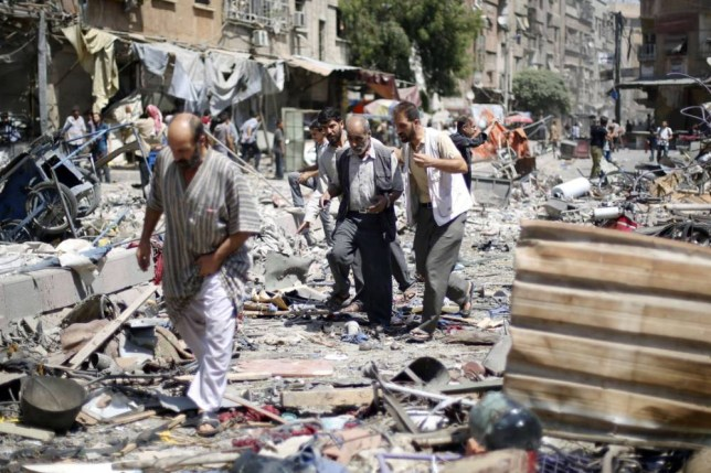 Syrian walk amid the rubble following air strikes by Syrian government forces on a marketplace in the rebel-held area of Douma, east of the capital Damascus, on August 16, 2015. At least 70 people were killed and 200 people were injured, with the death toll -most of them civilians- likely to rise as many of the wounded were in serious condition, the Syrian Observatory for Human Rights said. AFP PHOTO / SAMEER AL-DOUMYSAMEER AL-DOUMY/AFP/Getty Images