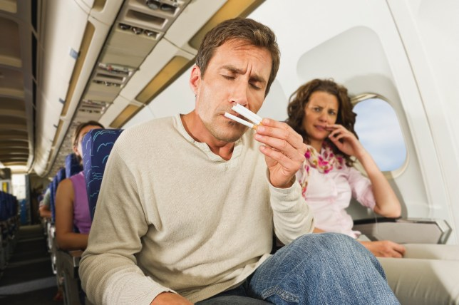 Germany, Munich, Bavaria, Man smelling cigarettes and women getting annoyed in economy class airliner