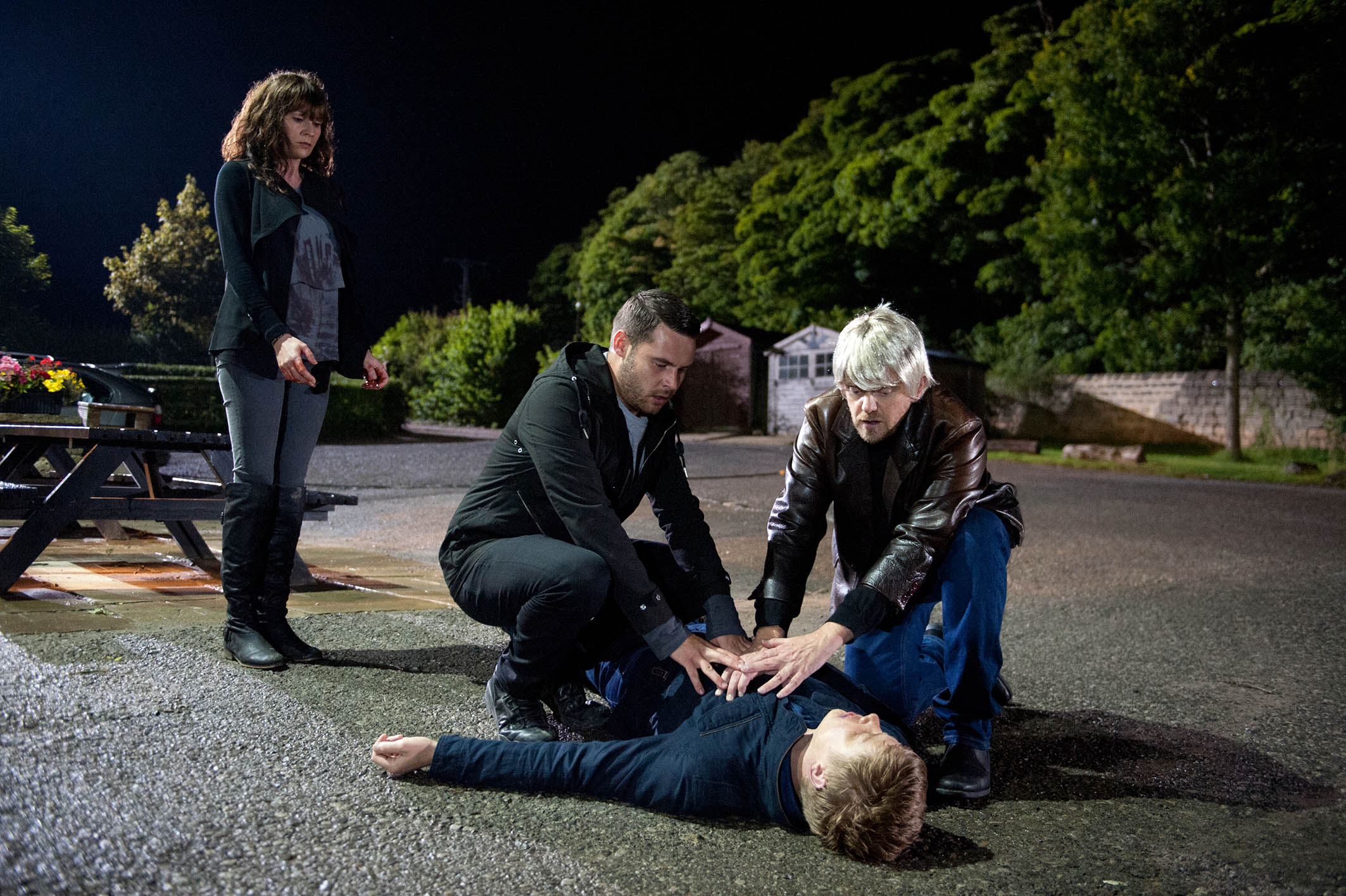 Robert Sugden [RYAN HAWLEY] slumps forward onto Chas Dingle [LUCY PARGETTER] after being shot. She manages to move him off her and stands up shakily, horrified as he bleeds. Lawrence arrives and Dan Spencer [LIAM FOX] jumps into action trying to save Robert. Bob leads a shocked Chas into the pub as the paramedics lift Robert into the ambulance. Lawrence calls Chrissie and leaves her an urgent message. Out walking on a road, Lachlan throws something into the hedge when he sees Lawrence's car and is visibly shaken when he's told that Robert's been shot. At the hospital, it's clear Robert's life hangs by a thread as a team of medics stand over him as Victoria Barton [ISOBEL HODGINS] tells Diane Sugden [ELIZABETH ESTENSEN] they should have stopped Andy. Robert flat lines and is rushed into surgery Picture contact: david.crook@itv.com on 0161 952 6214 This photograph is (C) ITV Plc and can only be reproduced for editorial purposes directly in connection with the programme or event mentioned above, or ITV plc. Once made available by ITV plc Picture Desk, this photograph can be reproduced once only up until the transmission [TX] date and no reproduction fee will be charged. Any subsequent usage may incur a fee. This photograph must not be manipulated [excluding basic cropping] in a manner which alters the visual appearance of the person photographed deemed detrimental or inappropriate by ITV plc Picture Desk. This photograph must not be syndicated to any other company, publication or website, or permanently archived, without the express written permission of ITV Plc Picture Desk. Full Terms and conditions are available on the website www.itvpictures.com