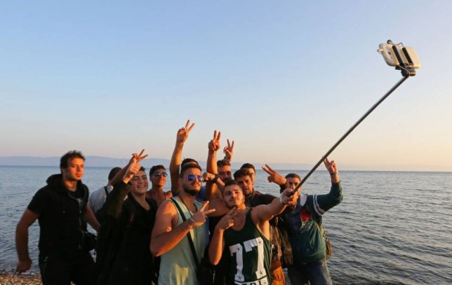 LESBOS ISLAND, GREECE - SEPTEMBER 06: Refugees flash victory sign as they pose for a selfie on the shore of Eftalou beach, north of the port city of Mytilini after crossing the Aegean from Turkey on September 06, 2015 in Lesbos Island, Greece. (Photo by Emin Menguarslan/Anadolu Agency/Getty Images)