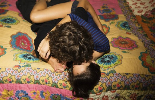 Teenage couple kissing on bed