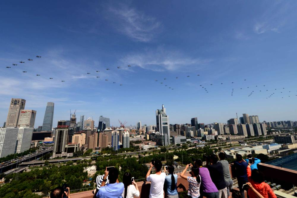 BEIJING, CHINA - SEPTEMBER 03: (CHINA OUT) Military helicopters fly over Beijing CBD (Central Business District) during a military parade at Tiananmen Square on September 3, 2015 in Beijing, China. China is marking the 70th anniversary of the end of World War II and its role in defeating Japan with a new national holiday and a military parade in Beijing. (Photo by ChinaFotoPress/ChinaFotoPress via Getty Images)