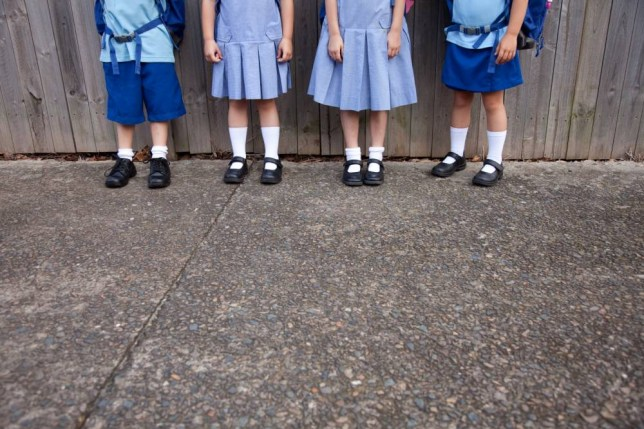 4 sets of legs of 5 yr olds in school uniform against a grey wooden fence