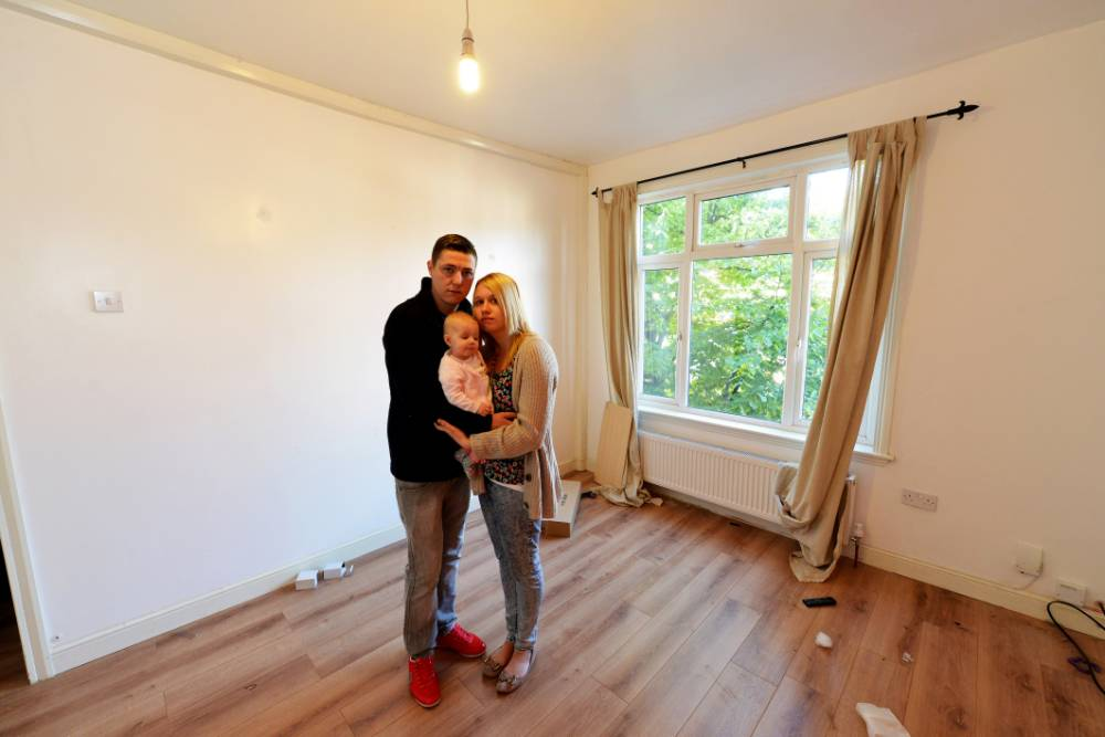PIC FROM CATERS NEWS - (PICTURED: Becky Szenk with her partner Mark Higgins and their baby Ariyah in the living room.) - A family has lost all of its worldly possessions after the removal men they hired drove off during a house move. Becky Szenk and Mark Higgins, from Walsall, west mids, had booked a removal firm that they had found on Facebook to move possessions from their flat to the pub that they manage. But after two removal men from the firm, named Lee Green, arrived in a rental van to pack up the familys property the Facebook page was taken down and the men have not been heard of since. SEE CATERS COPY.