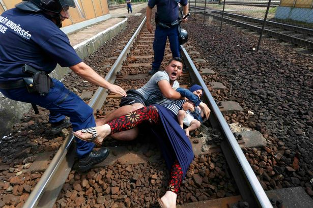 Families of refugees throw themselves onto railway track in Hungary