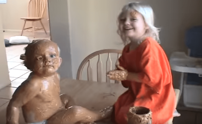 little girl caught covering baby brother with a tub of peanut butter
